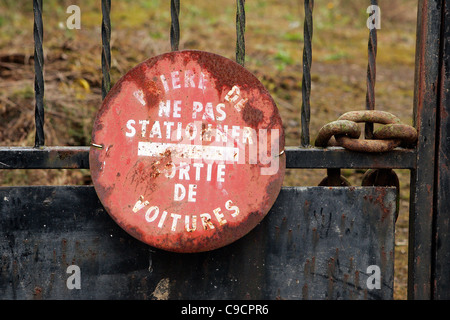 France, Brittany, Moustoir-Remungol, Rusty No Parking sign in French,  locked gate - Stock Photo