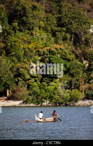 Two young boys 8-11 years paddle their outrigger dugout canoe off Mamoko island, Madagascar. Tropical forest in - Stock Photo