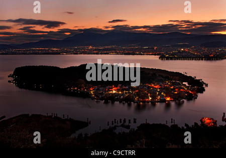 Panoramic sunset  view of Ioannina town, its lake ('Pamvotis' or 'Pamvotida'), the islet of the lake and its village. - Stock Photo