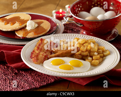 Eggs, sausage, bacon and potato breakfast with a stack of pancakes - Stock Photo