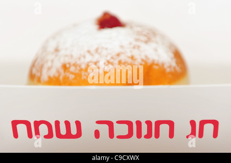 A doughnut in a box reading 'happy hanukkah holiday' for the Jewish holiday of Hanukkah - Stock Photo