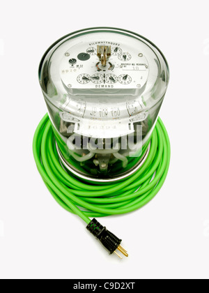 Electrical supply meter with a green electrical power cord and a black plug - Stock Photo
