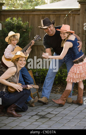 Family playing country music and dancing - Stock Photo