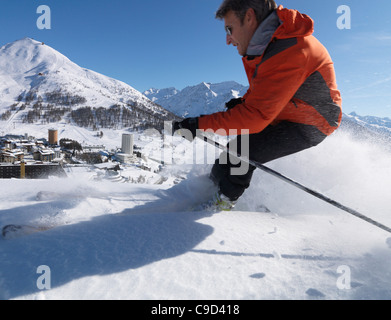 Italy, Piedmont, Sestriere village and ski resort (site of 2006 winter Olympics), with skier in foreground - Stock Photo