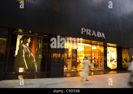 Japan, Honshu, Tokyo, Ginza, shopper walking by the Prada store on Chou-dori Avenue. - Stock Photo