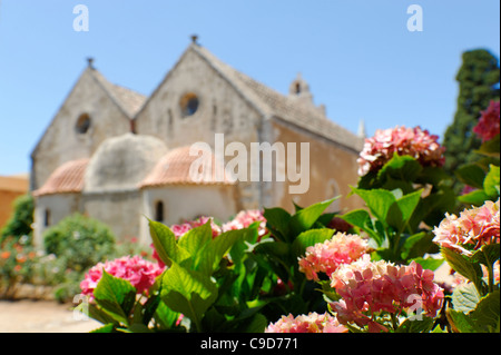 View over colored flowers of the rear of the beautiful golden stone Venetian church inside the Monastery of Arkadiou - Stock Photo