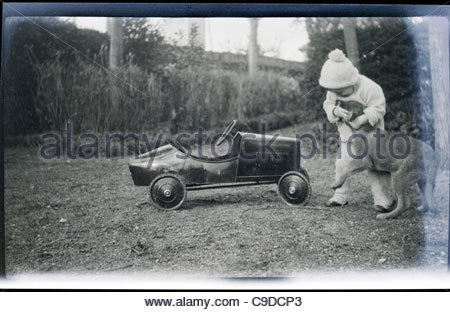 young child playing outdoors with dog 1920s - Stock Photo