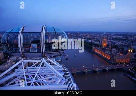 View of passenger pod capsule, Houses of Parliament, Big Ben and the River Thames from the London Eye at dusk,  - Stock Photo