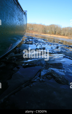 detail of the side of a green canoe breaking through icy water - Stock Photo
