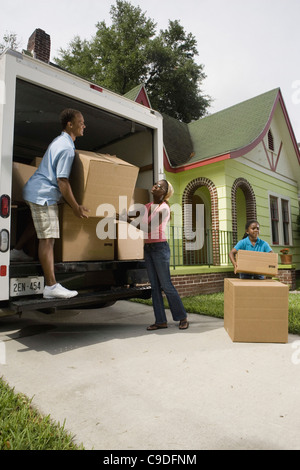 Family unloading boxes from moving truck - Stock Photo