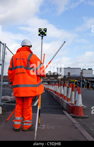 Building surveyor in a Hi-Viz jacket and trousers taking levels. - Stock Photo