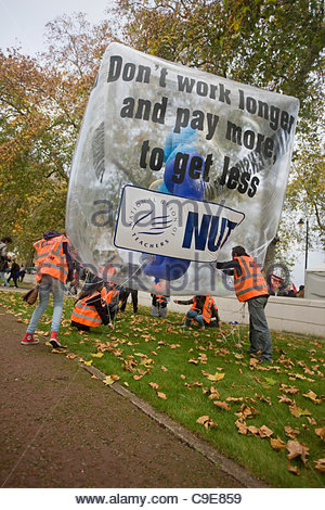 London, UK. 30th Nov, 2011. Protesters deflate their promotional balloon after the  public sector workers demonstration - Stock Photo
