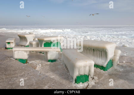Icy cafe tables and benches on the beach of the frozen Black Sea, a rare phenomenon, last time it occured in 1977, - Stock Photo