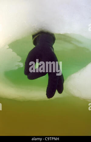 Diver's hand giving the OK sign, subglacial diving, ice diving, in the frozen Black Sea - Stock Photo