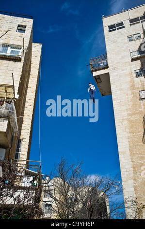 A figure of Haman hangs 'to death' from an eighth story balcony, symbolizing Haman's destiny as described in the - Stock Photo