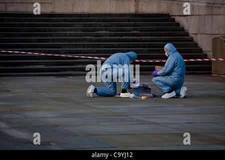 London, UK, 08, 03, 2012, Police forensics officers investigate the site of the explosion of the suspect package - Stock Photo