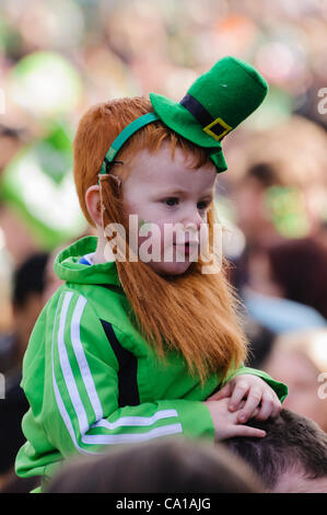 Belfast, UK. 17 Mar, 2012. Young boy on parents shoulders wearing a green hat and red/ginger beard on St Patrick's - Stock Photo