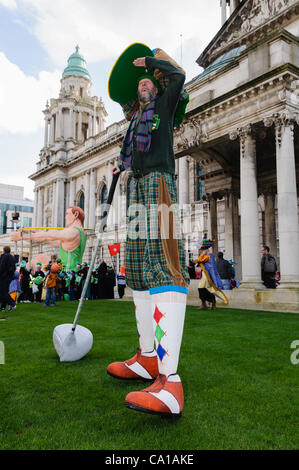 Belfast, UK. 17 Mar, 2012. Stiltwalker dressed as a giant golfer outside Belfast City Hall on St Patricks Day - Stock Photo