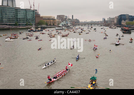 Numerous small boats proceed along River Thames past HMS Belfast as part of the Queen's Thames Diamond Jubilee Pageant, - Stock Photo