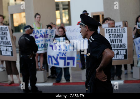 Israeli protesters holding placards against on going killing of innocent civilians by the Syrian regime and against - Stock Photo