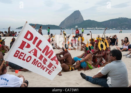 Indigenous people and others are beginning to assemble the human banner on Flamengo beach with the Sugarloaf in the background to protest about the construction of hydroelectric dams on Brazil's rivers. One participant carries a flag, 'Dilma Pare Belo Monte' - 'Dilma [Brazil's president] Stop Belo Monte'. The People's Summit at the United Nations Conference on Sustainable Development (Rio+20), Rio de Janeiro, Brazil, 19th June 2012. Photo © Sue Cunningham.