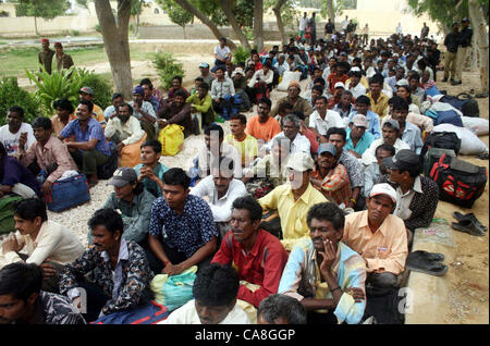 Freed Indian fishermen, who were imprisoned for violating  territorial waters, sit in queues before their release - Stock Photo