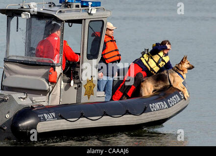 Aboard a Contra Costa County Sheriff's boat, CARDA dog handler Song Kowbell watches her Search and Rescue dog  Zippy - Stock Photo