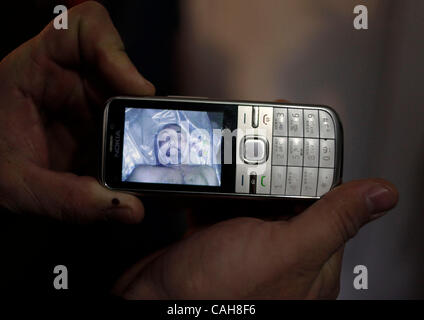 Nov 24, 2010 - Dagestan, Russia - A mother holds a mobile phone with a picture of her husband, who was abducted - Stock Photo
