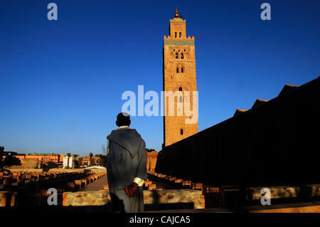Jan 21, 2008 - Marrakech, Morocco - A man wearing the traditional Moroccan djellaba looks toward the Koutoubia Mosque - Stock Photo