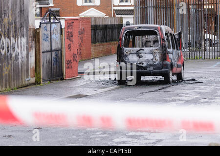 A burned out van is cordoned off by police after it was involved in a crime. - Stock Photo