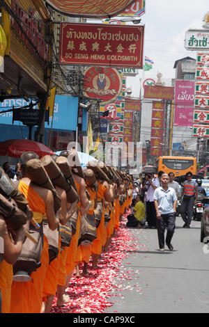 Bangkok, Thailand. 05 April 2012. Thai Buddhist monks walk on rose petals scattered by devotees. More than a thousand - Stock Photo