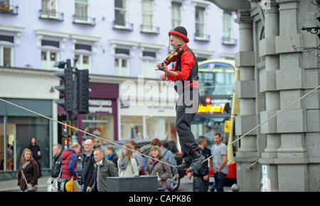 Brighton, UK. 07 April, 2012. Hitting the high notes a busker playing a violin performs on a tightrope during the - Stock Photo