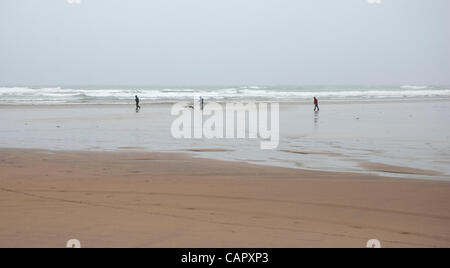 Three brave people wrapped up against the elements on a cold, rainy, windswept and deserted Summerleaze Beach on - Stock Photo