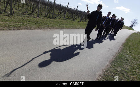 Boys in folk customs carry a giant 'pomlazka' (plated willow stems) to whip girls during traditional celebration - Stock Photo