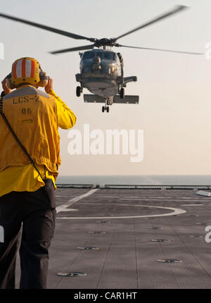 Florida 10th April 2012, Boatswain's Mate 3rd Class Robert Chittenden signals and MH-60R Seahawk, assigned to the - Stock Photo