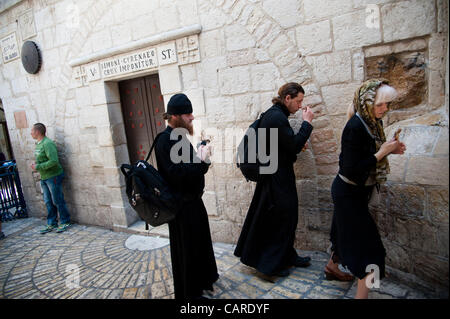 JERUSALEM - APRIL 13: Russian Orthodox priests and pilgrims stop at the Fifth Station of the Cross along the Via - Stock Photo