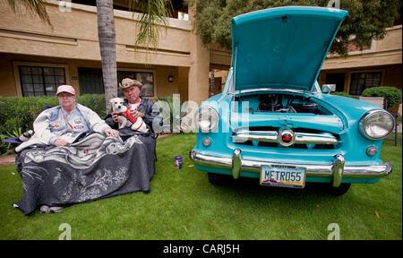 April 14, 2012 - Phoeniz, AZ, USA -  Bob and Yvonne McKenzie and their dog Max pose next to their 1955 Nash Metropolitan, - Stock Photo