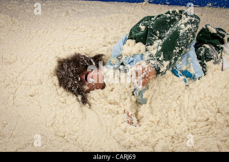 A competitor rolls around in a pool of instant grits during the grits roll competition at the World Grits Festival - Stock Photo