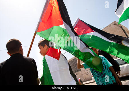 EAST JERUSALEM, PALESTINIAN TERRITORIES - APRIL 20: Palestinian youth wave flags while protesting the confiscation - Stock Photo