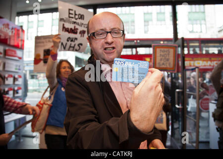 LONDON, UK, 21st Apr, 2012 A protester with a novelty NHS credit card inside a Virgin store on Oxford Street. They - Stock Photo
