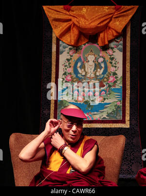 April 28, 2012 - Ottawa, Ontario, Canada - Dalai Lama adjusting his headphone while he addresses the audience during - Stock Photo