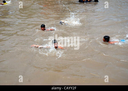 People take bath to beat the heat in a canal during hot weather in Gujranwala on Friday, May 11, 2012. - Stock Photo