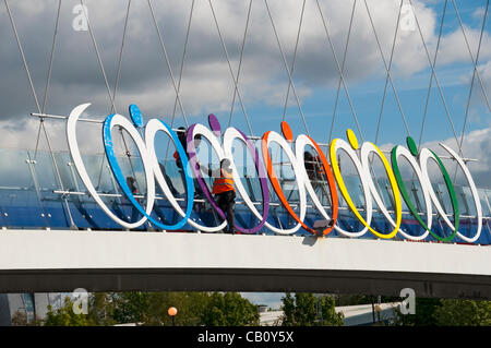 Workman installing an artwork on the Millennium (Lowry) footbridge in preparation for the Looping the Loop event - Stock Photo
