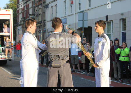CARDIFF, UK, 26th May 2012. An official supervises as Zak Lee Green (right) hands the Olympic flame over to the - Stock Photo