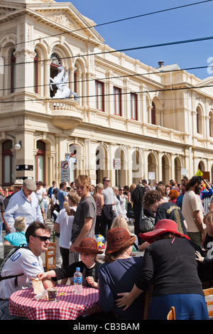 High Noon community festival is a Northcote local music fest in Melbourne, Australia family enjoy café table in the busy street.
