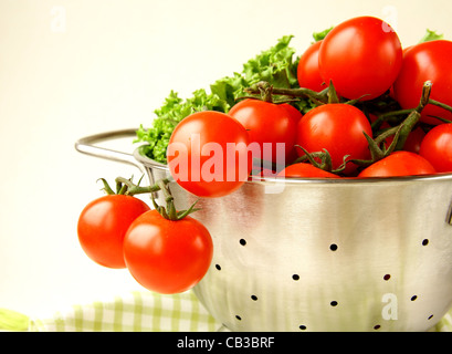 Fresh vegetables in metal colander over white - Stock Photo