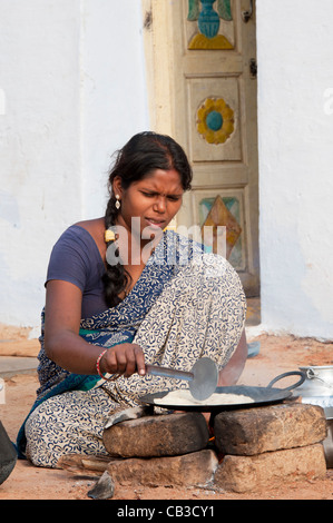 Young indian wife in a rural village making chapati on an open fire outside her home. Andhra Pradesh, India - Stock Photo