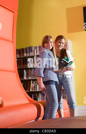 Teenagers hanging out in school library - Stock Photo