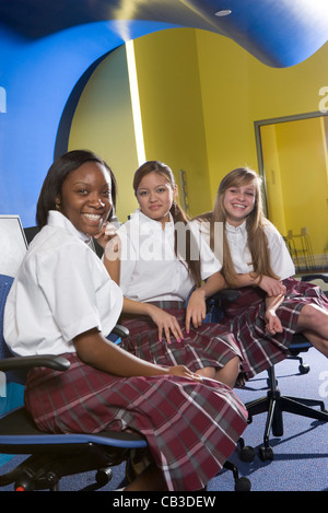 Portrait of three teenage girl students wearing uniforms in a classroom - Stock Photo