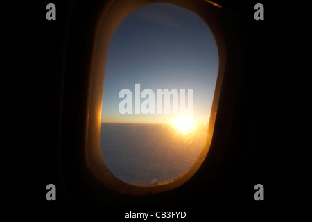 sunrise through passenger aircraft window during flight - Stock Photo